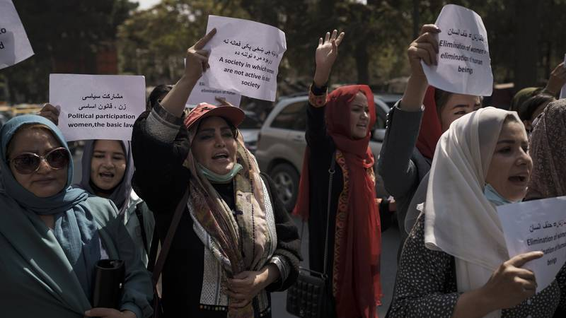 Women march to demand their rights under the Taliban rule during a demonstration near the...